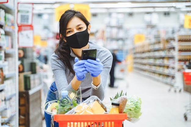 スーパーマーケットで買い物をしながらスマートフォンを手に持って保護マスクと手袋で笑顔の若い女性の肖像画。