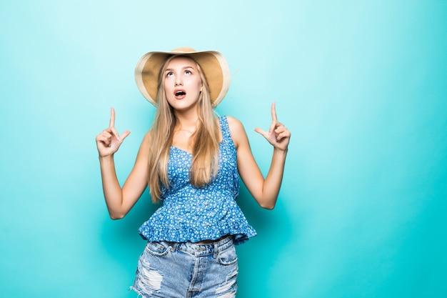 わらの夏の帽子、黄色の背景で隔離のコピースペースに人差し指を指しているオレンジ色のメガネで笑顔の若い女性の肖像画。