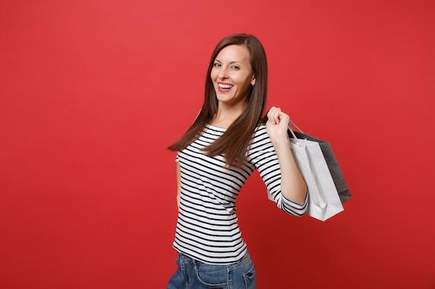 줄무늬 옷을 입은 웃고 있는 젊은 여성의 초상화는 붉은 벽 배경에서 격리된 쇼핑을 한 후 구매한 패키지 가방을 들고 있습니다. 사람들은 진심 어린 감정, 라이프 스타일 개념입니다. 복사 공간을 비웃습니다.