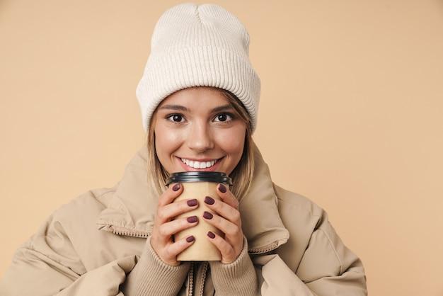 Портрет улыбающейся молодой женщины в зимнем пальто, держащей бумажный стаканчик и смотрящей в камеру