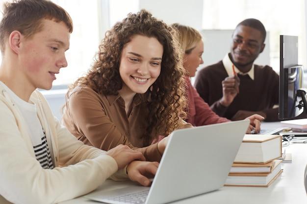 대학 도서관에서 학생들의 그룹과 함께 공부하는 동안 노트북 화면을보고 웃는 젊은 여자의 초상화
