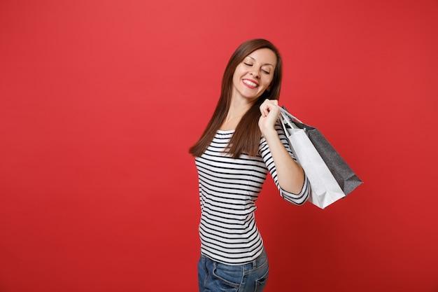 붉은 벽 배경에 격리된 손에 쇼핑을 한 후 구매한 패키지 가방을 뒤돌아보며 웃고 있는 젊은 여성의 초상화. 사람들은 진심 어린 감정, 라이프 스타일 개념입니다. 복사 공간을 비웃습니다.