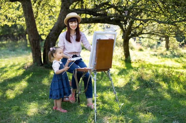Портрет улыбающейся молодой женщины-матери, показывающей свою маленькую дочь, рисующей картину на мольберте, весело вместе и проводящих свободное время на открытом воздухе в зеленом весеннем парке или саду. копировать пространство