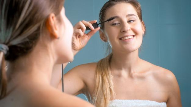 아침에 샤워를 한 후 마스카라로 그녀의 속눈썹을 그림 웃는 젊은 여자의 초상화.