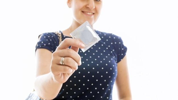 白でコンドームを示す笑顔の若い女性の肖像画。避妊とセックスの安全性の概念。