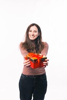 Портрет улыбающейся молодой женщины, стоящей на белом фоне, давая красную подарочную коробку
