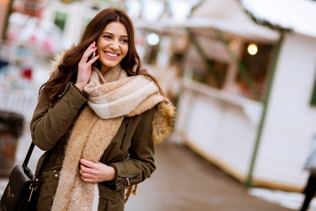 寒い冬の日に公園で電話を使用して笑顔の若い女性の肖像画