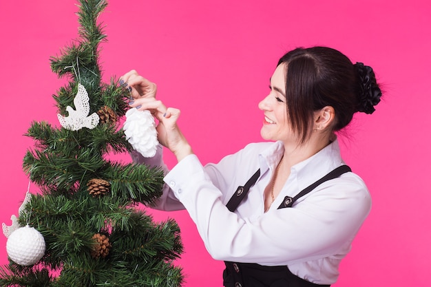 핑크에 크리스마스 트리 웃는 젊은 여자의 초상화