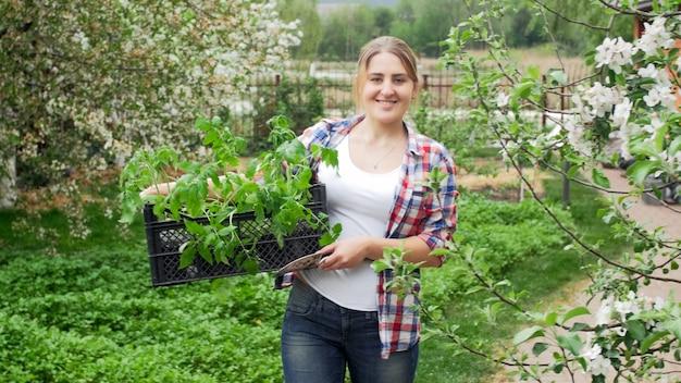 裏庭の庭でポーズをとって苗でいっぱいの木枠と笑顔の若い女性の肖像画。