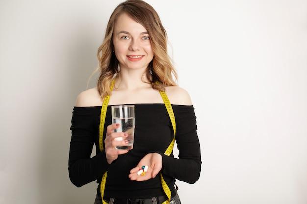 オメガ3魚油カプセルと笑顔の若い女性の肖像画。