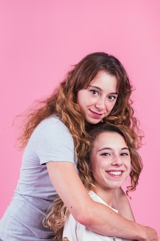 Portrait of smiling young women against pink backdrop