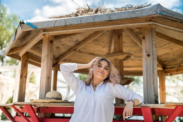 木製の望楼の砂浜の近くで、休暇を楽しんでいる笑顔の若い女性の肖像画。