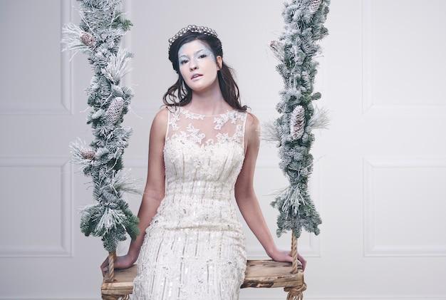 ブランコに座っている雪の女王の肖像画