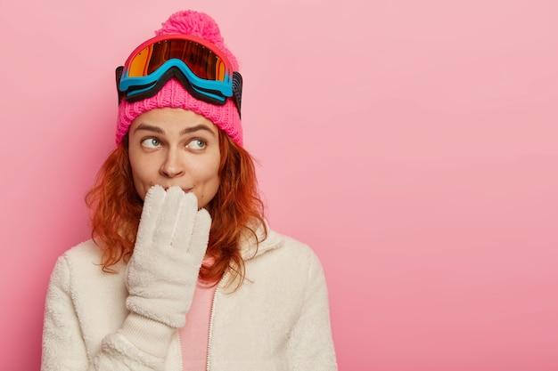 스노 여자의 초상화는 사려 깊은 표정을 가지고 입에 손을 유지하고 겨울 모자, 흰 장갑을 착용