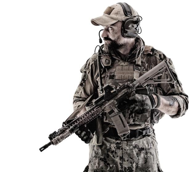 彼の肩に武器を持つフィールドユニフォームの特殊部隊の兵士の肖像画、白で隔離の肖像画