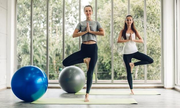 スポーツウエアでスポーツの魅力的な人々の女性の肖像画はリラックスしてスポーツクラブでクラスのトレーニングで青いフィットボールでヨガフィットネス運動を練習