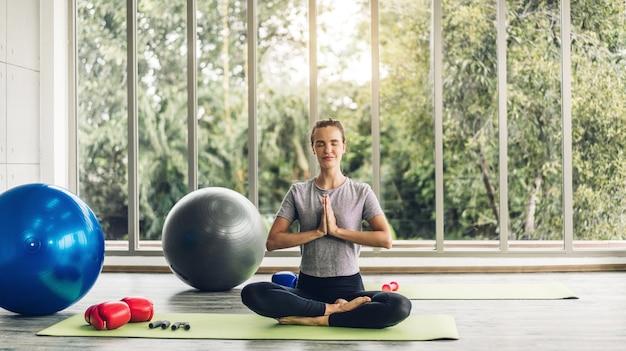 Портрет спортивной женщины в спортивной одежде, расслабляющейся и практикующей фитнес-упражнения йоги с синим фитболом дома