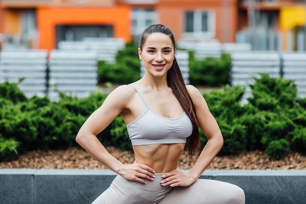 Портрет, спортивная брюнетка женщина делает упражнения на корточках на улице.