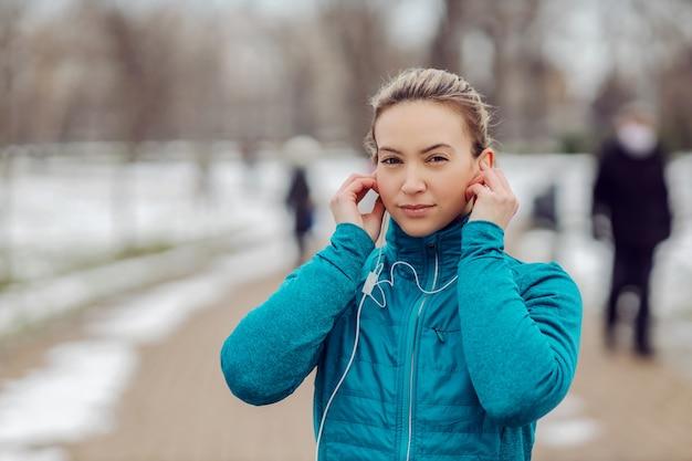 Портрет спортсменки в теплой одежде, стоящей в общественном парке в снежную погоду и надевающей наушники.
