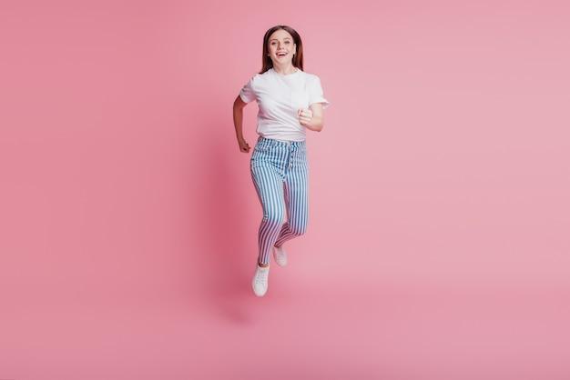 Портрет спортивной активной сумасшедшей девушки, прыгающей в воздухе, в повседневной джинсовой одежде на розовой стене