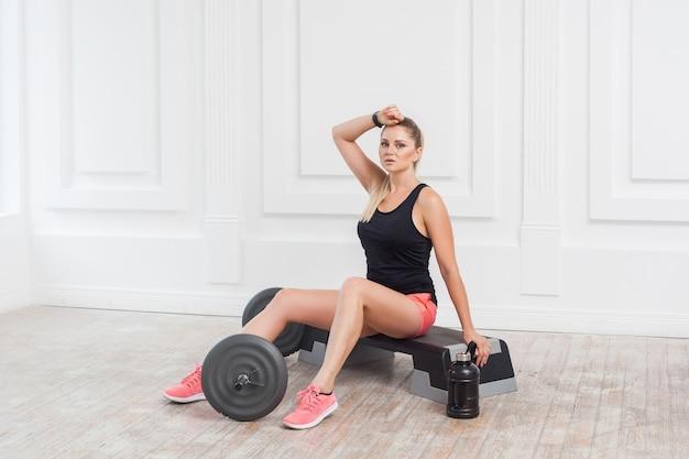 분홍색 반바지와 검은색 상의를 입은 스포티하고 아름다운 젊은 운동 금발 여성의 초상화는 땀을 흘리며 체육관에서 열심히 일한 후 휴식을 취합니다. 실내, 스튜디오 촬영, 스포츠 개념, 카메라를 보고
