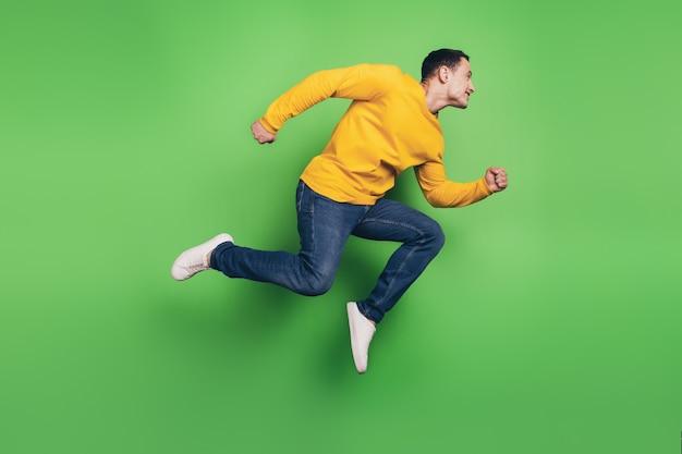 スポーティでエネルギッシュな男のジャンプランの肖像画は、緑の背景に空のスペースを見てください