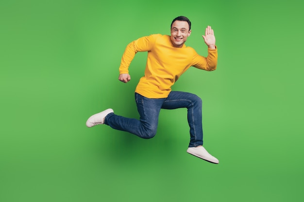スポーティでエネルギッシュな男のジャンプラン波の手の肖像画は緑の背景に挨拶します