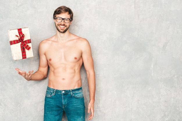 スポーティなハンサムな強い男の肖像画。ジーンズの灰色の壁の近くでポーズをとる健康的な運動フィットネスモデル。