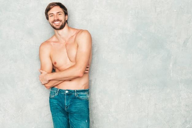 スポーティなハンサムな強い男の肖像画。ジーンズの灰色の壁の近くでポーズをとる健康的な笑顔の運動フィットネスモデル。