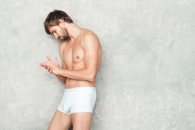 スポーティなハンサムな強い男の肖像画。白い下着の灰色の壁の近くでポーズをとる健康的な笑顔の運動フィットネスモデル。