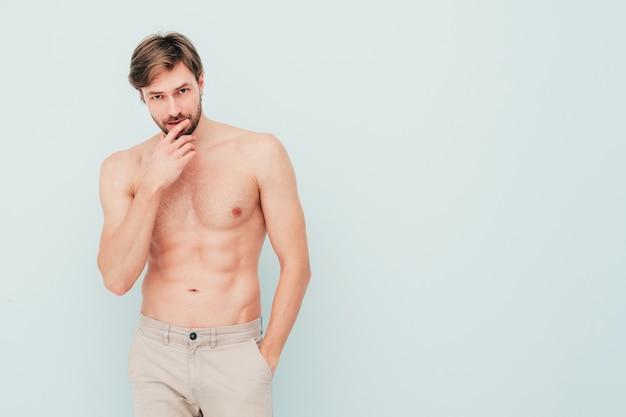 スポーティなハンサムな強い男の肖像画。水色の壁の近くでポーズをとる健康的な笑顔の運動フィットネスモデル