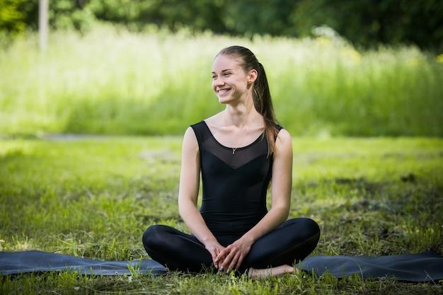 Портрет спортивной женщины, делающей упражнения на растяжку в парке перед тренировкой