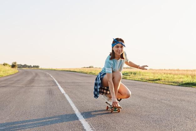 Портрет спортивной женщины в повседневной одежде, сидящей на корточках на скейтборде, смотрящей вдаль с концентрированным выражением лица, наслаждающейся скейтбордингом, здоровым образом жизни.