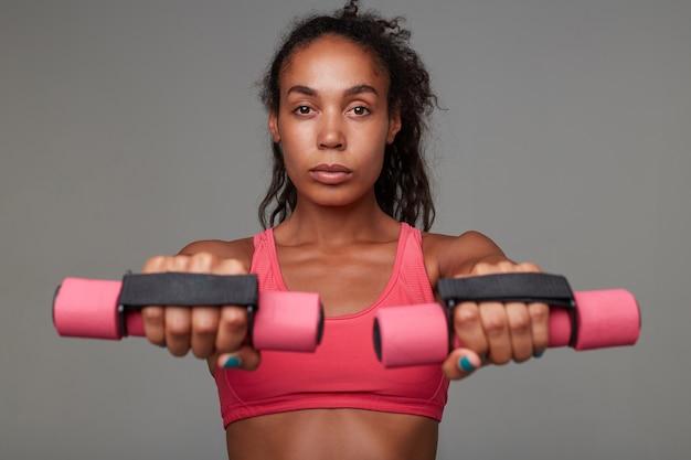 Портрет спортивной молодой кареглазой темнокожей кудрявой дамы, держащей утяжелители в поднятых руках и смотрящей на амеру со спокойным лицом, в спортивном розовом топе
