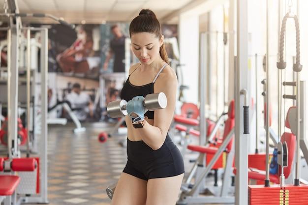 Портрет спортивной молодой леди в идеальной физической форме позирует посреди спортивного зала
