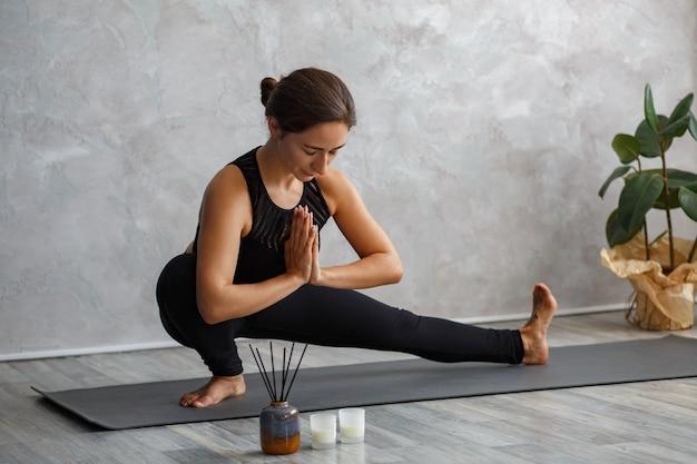 Портрет спортивной молодой женщины, делающей упражнения на уроке йоги дома. красивая девушка практикует позу выпада в сторону, скандасану.