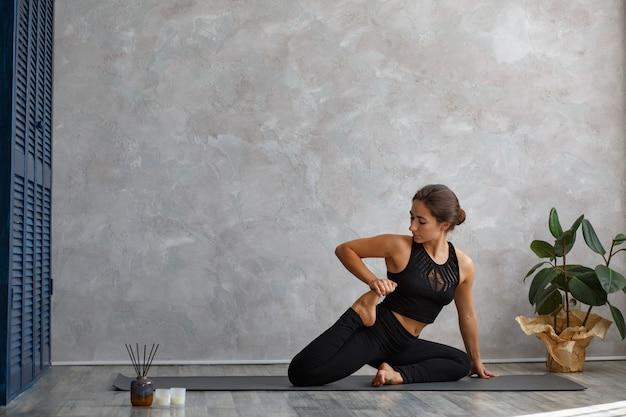Портрет спортивной молодой женщины, делающей упражнения на уроке йоги дома.