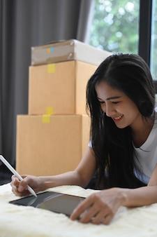 デジタルタブレットを使用してスタートアップ中小企業の起業家の肖像画は、彼女のスタートアップホームオフィスで顧客から注文を受けます。