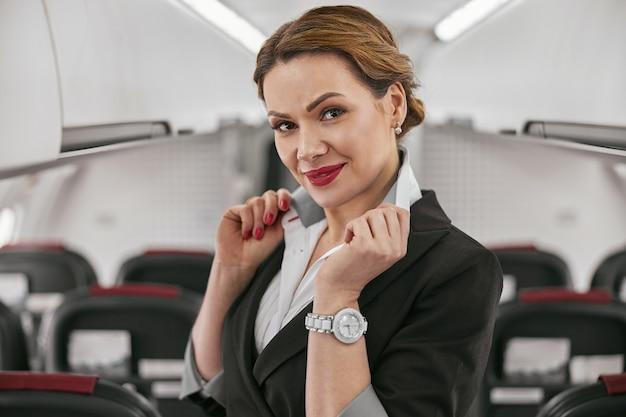 飛行機のジェット機の客室のスチュワーデスの肖像画。モダンな飛行機のインテリアのぼかし。笑顔のヨーロッパの女性は制服を着てカメラを見ています。民間商用航空。空の旅のコンセプト