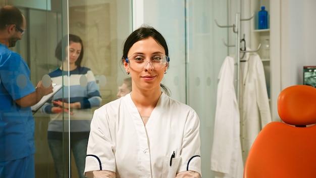 간호사가 백그라운드에서 환자와 이야기하는 동안 치과 사무실에 있는 카메라에 미소 stomatologist의 초상화. 치과 의사는 구강 클리닉의 의자에 앉아 웹캠을 보고 있습니다.