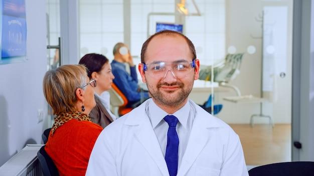 Портрет стоматолога, улыбаясь в камеру, находящуюся в стоматологическом кабинете, пока пациенты ждут его в фоновом режиме. врач-стоматолог смотрит на веб-камеру, сидя на стуле в стоматологической клинике.
