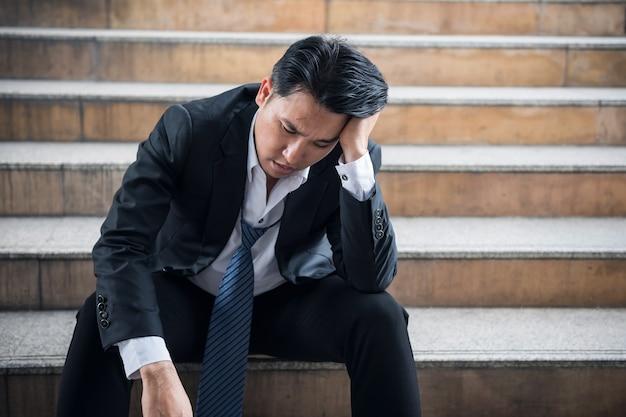 悲しい感じで階段に座っているストレス絶望的な上級ビジネスマンの肖像画の肖像