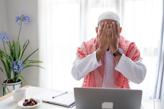 ノートパソコンを使用してストレスのイスラム教徒の男性の肖像画は、自宅で仕事中に手で顔を覆います