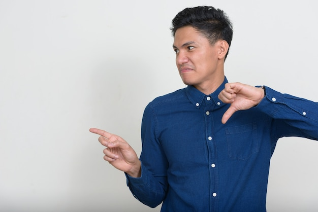Портрет подчеркнутого азиатского бизнесмена, выглядящего с отвращением