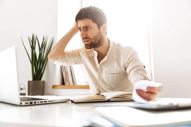 Портрет подчеркнутого бизнесмена 30-х годов в белой рубашке, работающего с ноутбуком и бумажными документами, сидя в ярком офисе