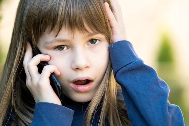 携帯電話で話している長い髪のストレスの多い子供の女の子の肖像画。スマートフォンを使用して通信する小さな女性の子供。子供のコミュニケーションの概念。
