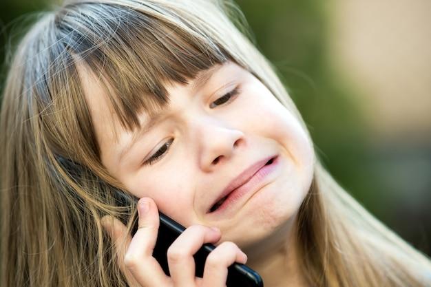 携帯電話で話している長い髪の重点を置かれた子供の女の子の肖像画。スマートフォンを使用して通信の小さな女性の子供。子供のコミュニケーションの概念。