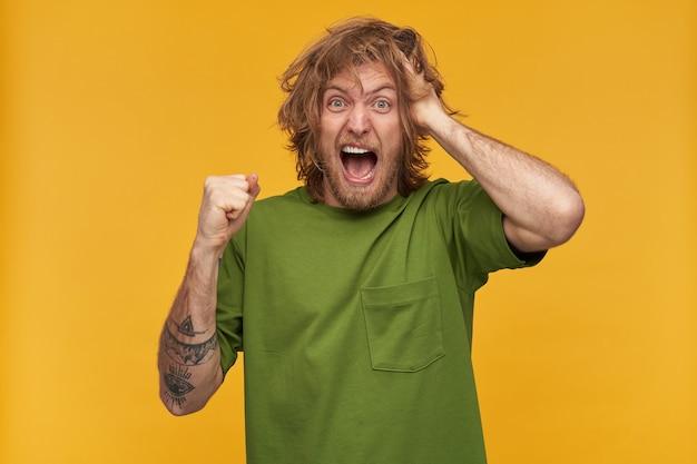 金髪の乱雑な髪型とあごひげを持つストレス、狂気の男性の肖像画。緑のtシャツを着ています。入れ墨があります。彼の拳を握り締めます。頭に触れる。黄色の壁に隔離 Premium写真