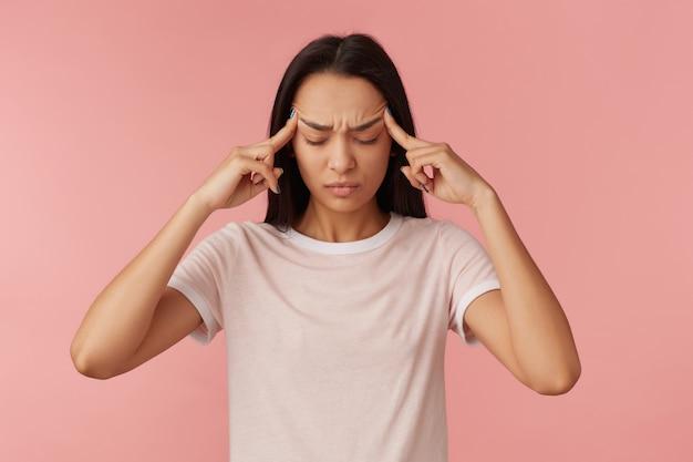 ストレスの多い、黒い長い髪の痛みの少女の肖像画。白いtシャツを着ています。人と感情の概念。彼女の寺院を揉んでマッサージします。頭痛がします。パステルピンクの壁の上に隔離されたスタンド