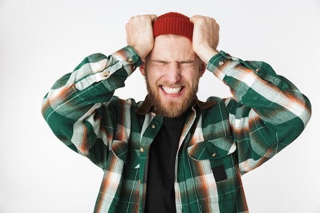 Портрет подчеркнутого мужчины в шляпе и клетчатой рубашке, кричащего и хватающегося за голову, стоя изолированно на белом фоне